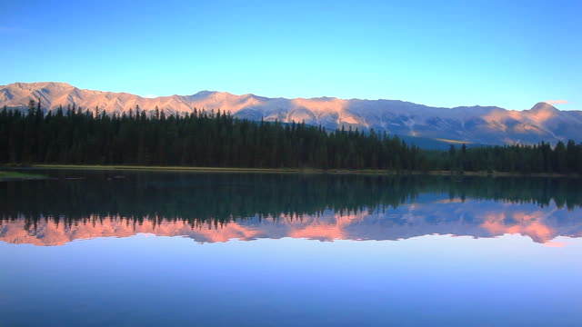 Mountains at sunset reflecting their glow in Alpine Lake video
