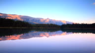 Mountains at sunset reflecting their glow in Alpine Lake video