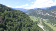 AERIAL: Mountains covered with rug of trees above small village in river valley video