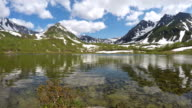 Mountains, mountain lake and clouds drifting across sky on sunny day video