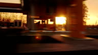 Movement along the Silhouette petrol station at sunset (POV) video