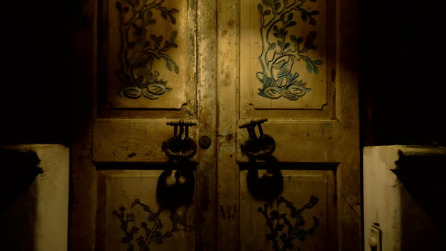 Moving away from the door with large handles and a keyhole in a vintage style. video