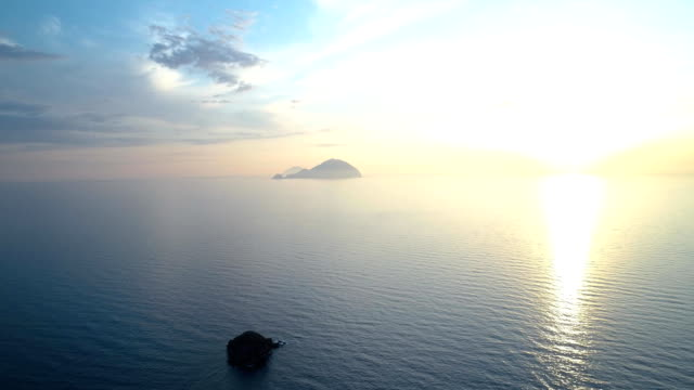moving backward aerial view of mediterranean sea ocean at sunset or sunrise with far islands.Nature outdoors travel establisher,Italy,Sicily Eolian Island.Summer or spring.4k drone establishing video video