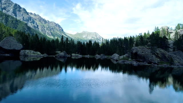 moving backward away from clear blue lake and pine woods forest mountain valley in summer.Europe Alps outdoor green nature scape mountains wild aerial establisher.4k drone flight establishing shot video
