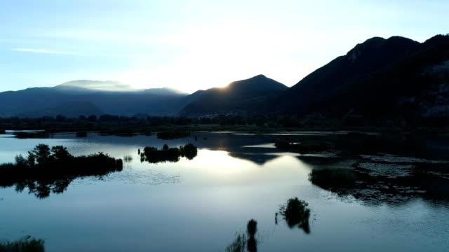 moving backward from sunrise lake in summer.Europe Italy outdoor green nature scape wild aerial establisher.4k drone flight establishing shot video
