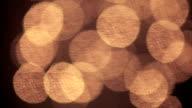 Moving gold sparkles on dark background. video
