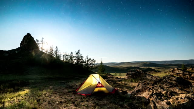 Moving moon above tent at night time lapse video