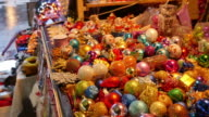 A moving shot from left to right of a Christmas market and a table full of colorful decoration balls video