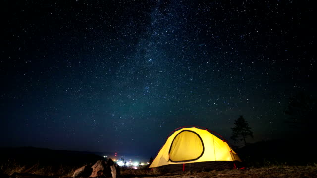 Moving stars above tent at night time lapse video
