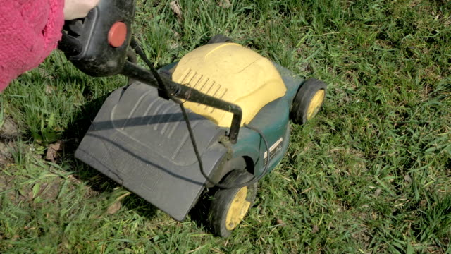 Mowing grass in the garden with electrical machine video