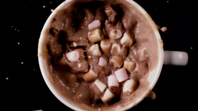 Much marshmallow falls into cocoa, top view. Slow mo video
