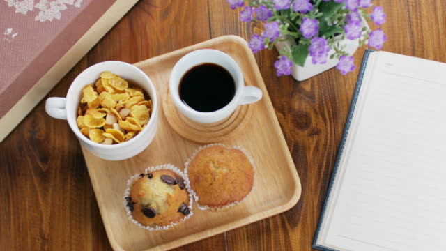 Muffin cake and gen food with black coffee breakfast set on wooden dish and wooden table, dolly shot right to left video