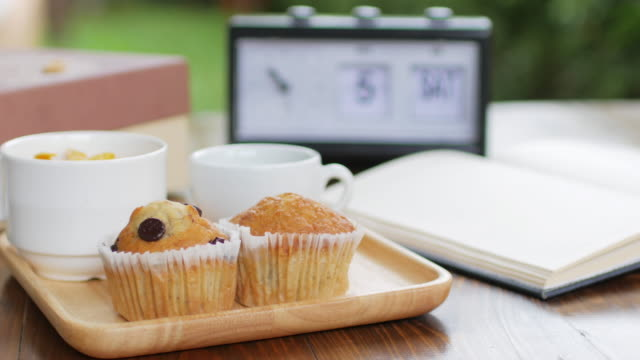 Muffin cake with black coffee breakfast set on wooden dish and wooden table, dolly shot right to left video