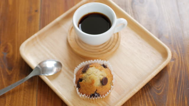 Muffin cake with black coffee on wooden dish and table , dolly shot left to right video