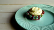 Muffin cake with butter cream on plate at wooden table. One cupcake with cream video
