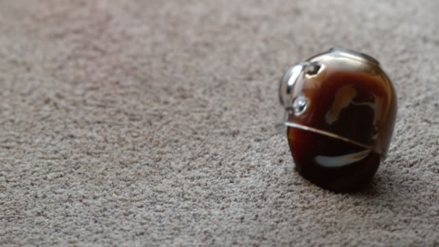 Mug of coffee spilling on carpet in slow motion video