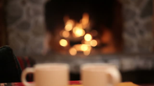 Mugs of hot cocoa with fireplace in background video