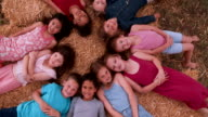 Multi ethnic Group of children lying in circle on straw video
