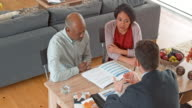 Multi ethnic senior couple consulting a personal banker at home video