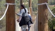 Multi generation black family crossing rope bridge, back view video