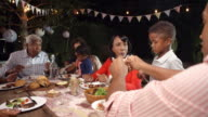 Multi generation black family eating food at table outdoors video