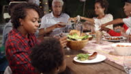 Multi generation black family serving food at table outdoors video