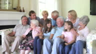 Multi Generation Family Group Sitting On Sofa Indoors video