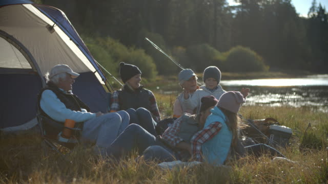 Multi generation family relaxing outside tent in countryside video