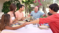 Multi Generation Family Say Prayer Before Meal On Terrace video