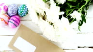 Multicolored Easter eggs, bunch of flower and envelope on wooden surface video