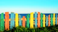 Multi-colored fence against the sea. video