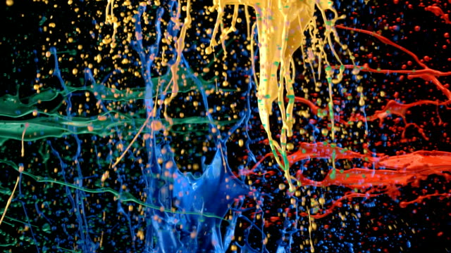 Multi-colored paint splattering in slow motion video