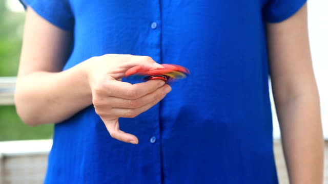 Multicolored, red-yellow-blue hand spinner, or fidgeting spinner, rotating on man's hand. Woman spinning a Fidget Spinner on the street video