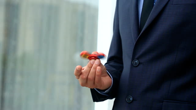 Multicolored, red-yellow-blue hand spinner, or fidgeting spinner, rotating on man's hand. Man in a suit spinning a fidget spinner on the street video