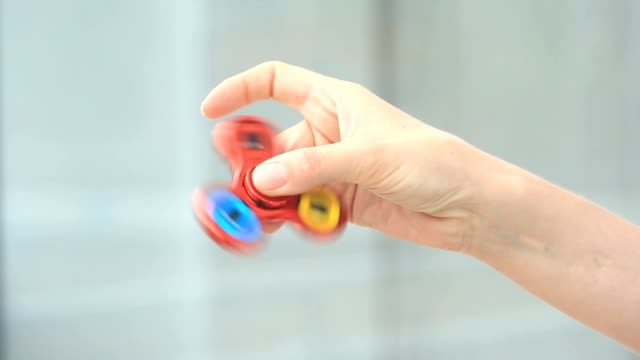 Multicolored, red-yellow-blue hand spinner, or fidgeting spinner, rotating on man's hand. video
