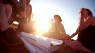 Multi-ethnic boho Girls eating pizza outdoor at sunset video