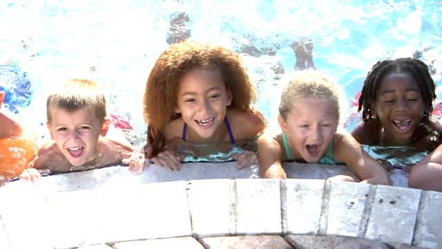 Multi-ethnic children hanging on side of swimming pool video