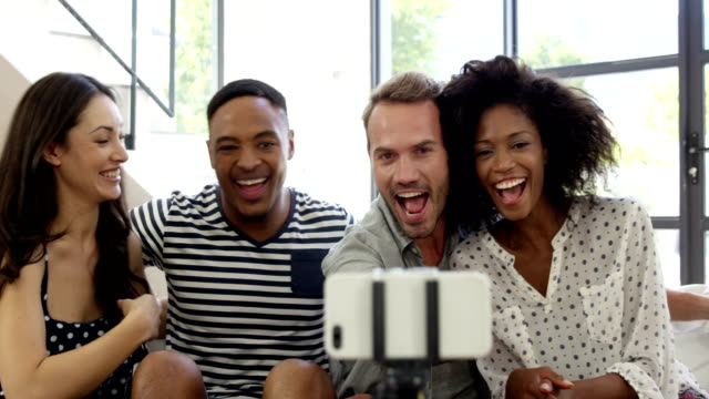 Multi-ethnic friends smiling and taking selfie video
