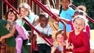 Multi-ethnic group of children laughing on playground video