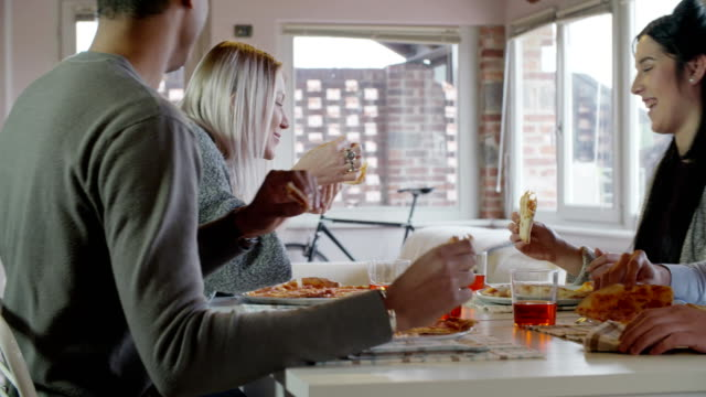 multiethnic group of friends people enjoy having lunch or dinner meal together eating pizza indoor in modern industrial house. 4k handheld slow motion video shot video