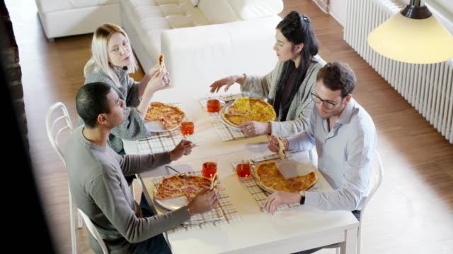 multiethnic group of friends people enjoy having lunch or dinner meal together eating pizza indoor in modern industrial house. 4k handheld slow motion top view overhead video shot video