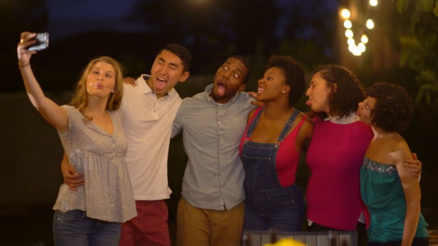 Multi-ethnic group of friends pulling faces whilst taking a selfie together video