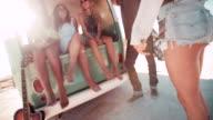 Multi-Ethnic group of friends sit in back of open retro van video