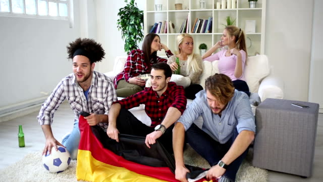 Multiethnic group of friends watching a football game video