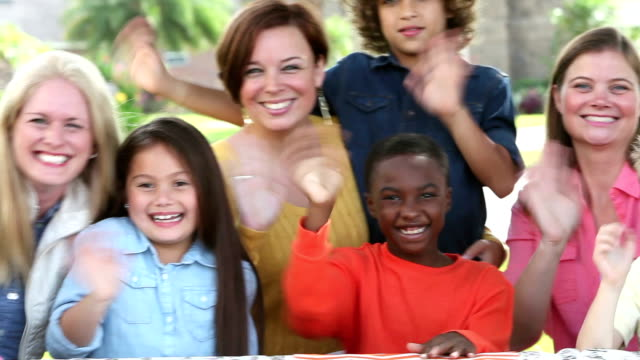 Multi-ethnic group of women, children waving at camera video