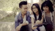 Multiethnic happy, college friends together sharing smart phone. video