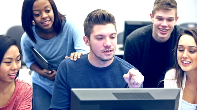 Multi-ethnic high school students in computer class around one monitor video