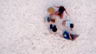 Multi-Ethnic Hipster Friends sitting on Sandy Beach and hug each other video