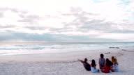 Multi-Ethnic Hipster Friends sitting on Sandy Beach video