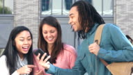 Multi-ethnic students looking and laughing at mobile phones video